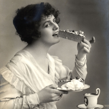 Beautiful Woman Eating Cheesecake Dessert. Image shot 1910. Exact date unknown.